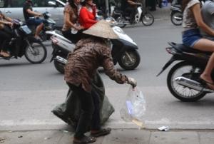 Một phụ nữ nhặt bao ni lông rơi vãi trên đường phố Hà Nội để bán kiếm ít tiền sống qua ngày.